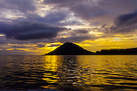 Indonesia, Sulawesi, Bunaken. Sunset at Bunaken. Manado Tua is a landmark with it's characteristic cone shape, a now extinct volcano.