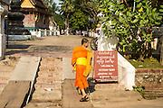 11 MARCH 2013 - LUANG PRABANG, LAOS:   A Buddhist novice walks into Wat Xieng Thong, the most historic Buddhist temple in Luang Prabang.  PHOTO BY JACK KURTZ