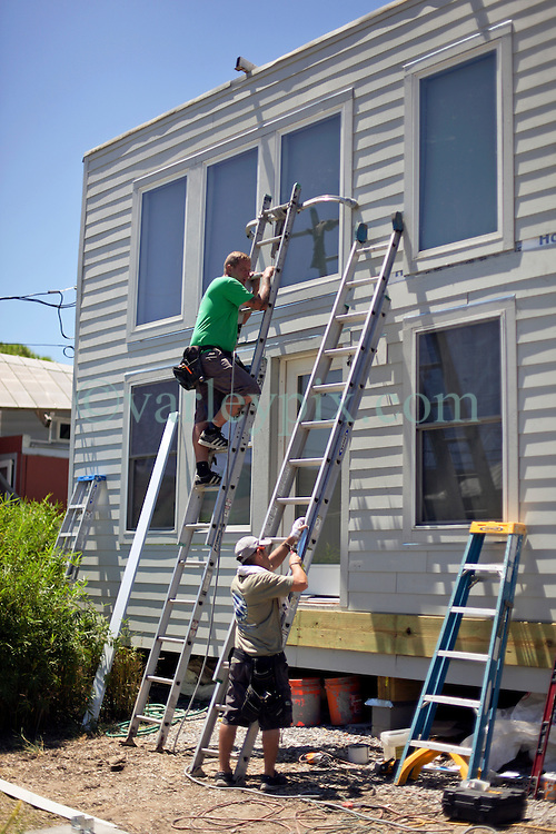 26 August 2015. New Orleans, Louisiana. <br /> Hurricane Katrina revisited. <br /> Rebuilding the Lower 9th Ward. <br /> Contractors with Caledonia Construction work on a new 'Make it Right' house on Tennessee Street. Eco friendly 'Make it Right' houses inspired by actor Brad Pitt continue to provide hope for the rebirth of the community following the devastation of hurricane Katrina a decade earlier.<br /> Photo credit©; Charlie Varley/varleypix.com.
