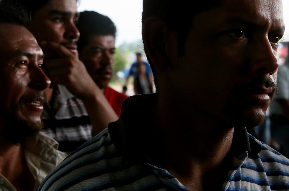Migrant farmers wait in line to get matricula identification cards. The card will allow the men to open a U.S. bank account as well as obtain a drivers license.