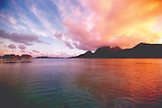 The sunset creates a myriad of colors over a tropical vacationer's dream resort in Tahiti