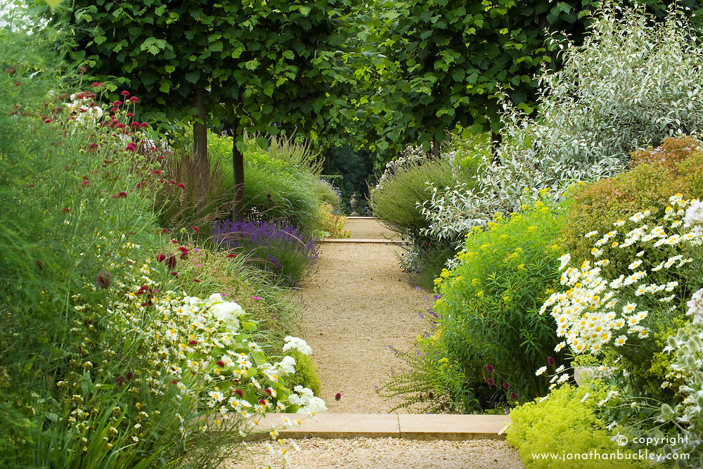 Gravel path and borders at Broughton Grange with stone urn as focal point