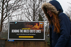 © Licensed to London News Pictures. 01/02/2021. London, UK. A woman walks past the government's 'Bending the rules costs lives' awareness publicity campaign poster in north London. Covid-19 infection rates are continuing to drop across London. According to a Government scientific adviser, the UK could be easing out of restrictions in March and back to almost normal by summer if vaccines are 70 to 80 per cent effective at blocking transmission. Photo credit: Dinendra Haria/LNP