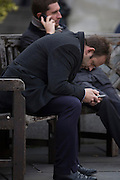 Two men using smartphones in a City of London street.