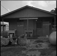 Undocumented Mexican workers pick tobacco in the sweltering heat of the eastern North Carolina tobacco fields. Many work barefoot in the mud exposing their feet to a toxic mixture of pesticides and nicotine which can cause their feet to turn black.  <br />    At the Carson Barns camp, the exterior of the outdoor bathroom facilities.