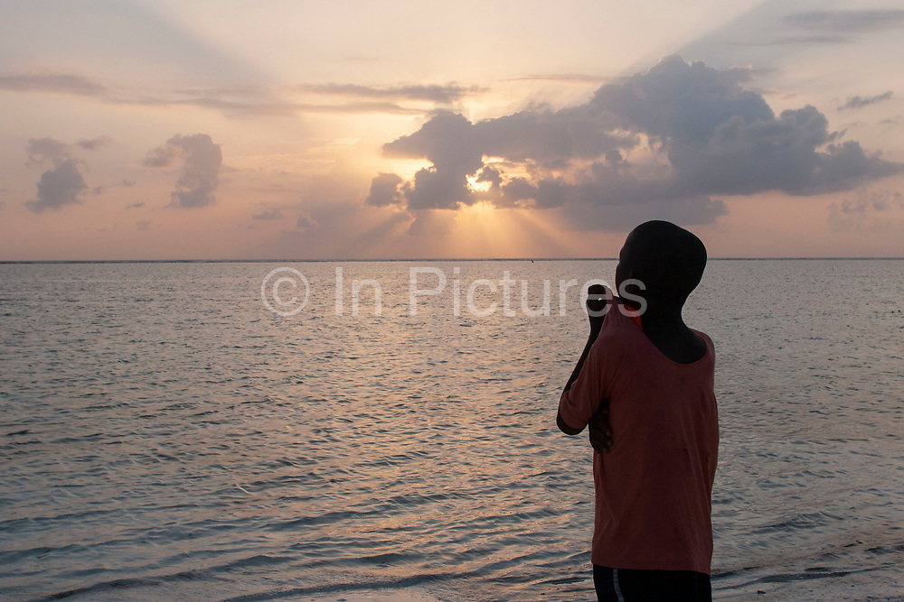A boy looks out to sea at sunset on Matemwe beach on 12th December 2008 in Zanzibar, Tanzania. Zanzibar is a small island just off the coast of the Tanzanian mainland in the Indian Ocean. In part due to its name, Zanzibar is a travel destination of mystical reputation, known for its incredible sealife on its many reefs, the powder white coral sand beaches and the traditional cultivation of spices.