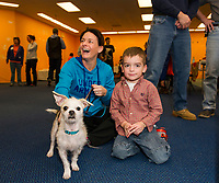 """Alissa and Matteo Perniciaro sit with """"Peyton"""" a 1 1/2 year old Terrier mix as Matteo's grandparents go through the adoption papers to give Peyton a forever home during the NH Humane Society's Adopt a thon at the Belknap Mall on Friday morning.  (Karen Bobotas/for the Laconia Daily Sun)"""