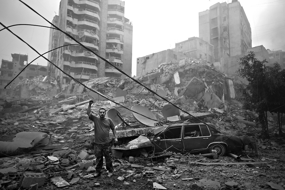 A Hezbollah militia man and resident of Haret Hreik in Beirut's southern suburbs, Lebanon, July 17, 2006. He gestures in front of the damaged neighborhood, a stronghold of the militant group Hezbollah, after a series of Israeli air strikes flattened much of the area.