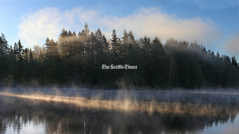 Early morning fall light streaks across the mist rising from Pine Lake on the Sammamish Plateau. (Steve Ringman / The Seattle Times)
