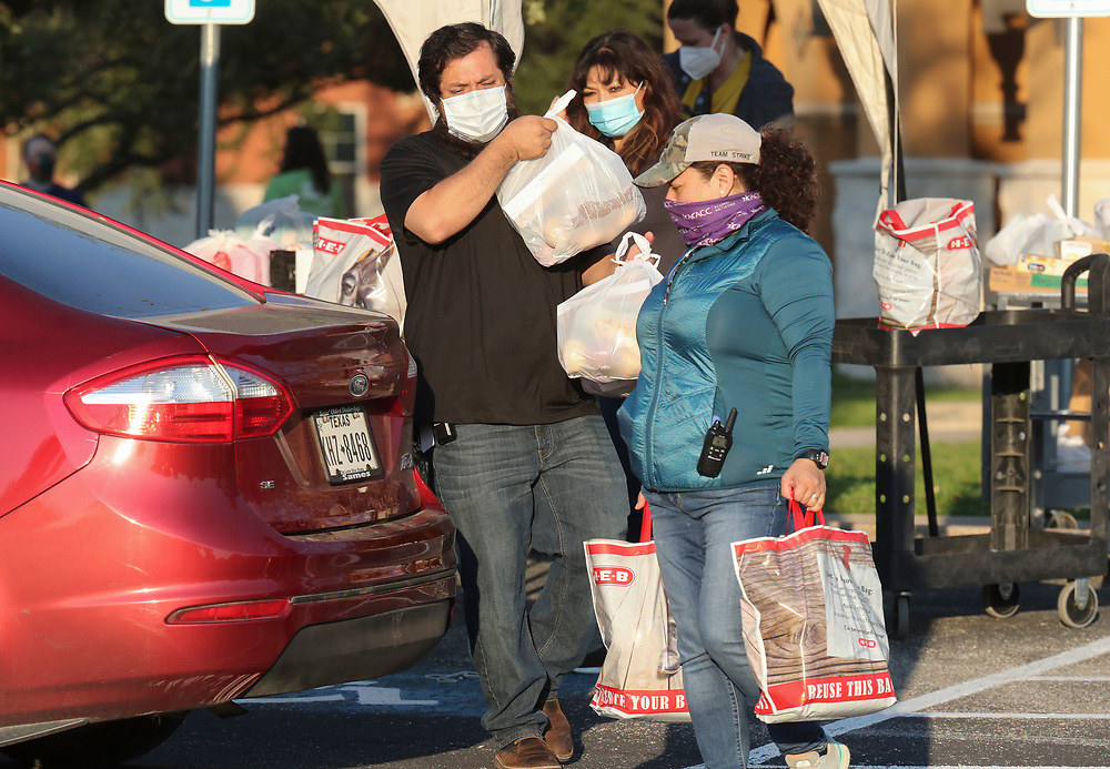 Staff members including Alejandro DelValle, and Arlene Lozano help conduct a twice-weekly fresh food drive sponsored by Catholic Charities helping low-income Texans  make ends meet in Austin. The October 1, 2020 effort helped several hundred family members with fruit, meats, milk and cereal.