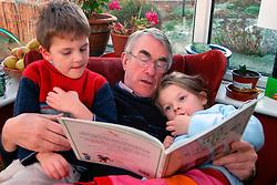 Grandfather reading Alfie book to his young grandchildren; UK