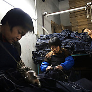 """Workers sew jeans using a sanding machine in Mr Huang's factory in Zhongshan city, China, while a child sleeps on a pile of jeans. .This picture is part of a photo and text story on blue jeans production in China by Justin Jin. .China, the """"factory of the world"""", is now also the major producer for blue jeans. To meet production demand, thousands of workers sweat through the night scrubbing, spraying and tearing trousers to create their rugged look. .At dawn, workers bundle the garment off to another factory for packaging and shipping around the world..The workers are among the 200 million migrant labourers criss-crossing China.looking for a better life, at the same time building their country into a.mighty industrial power."""