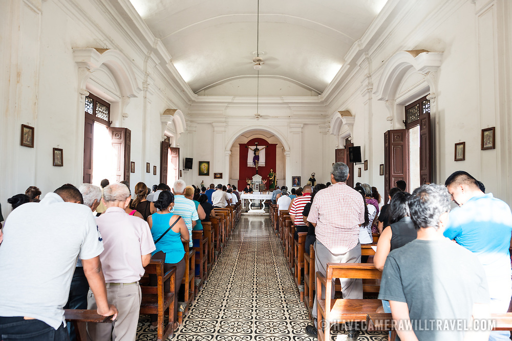 During a Sunday morning mass at the chapel at Granada Cemetery. The chapel, near the cemetery's entrance, was constructed in 1922. Granada Cemetery is Nicaragua's oldest cemetery and was, between the period 1876 and 1922, widely used as the final resting place of many of country's political and cultural elite, including six Nicaraguan presidents. Most of its tombs and mausoleums are above ground and in stark white stucco and marble.
