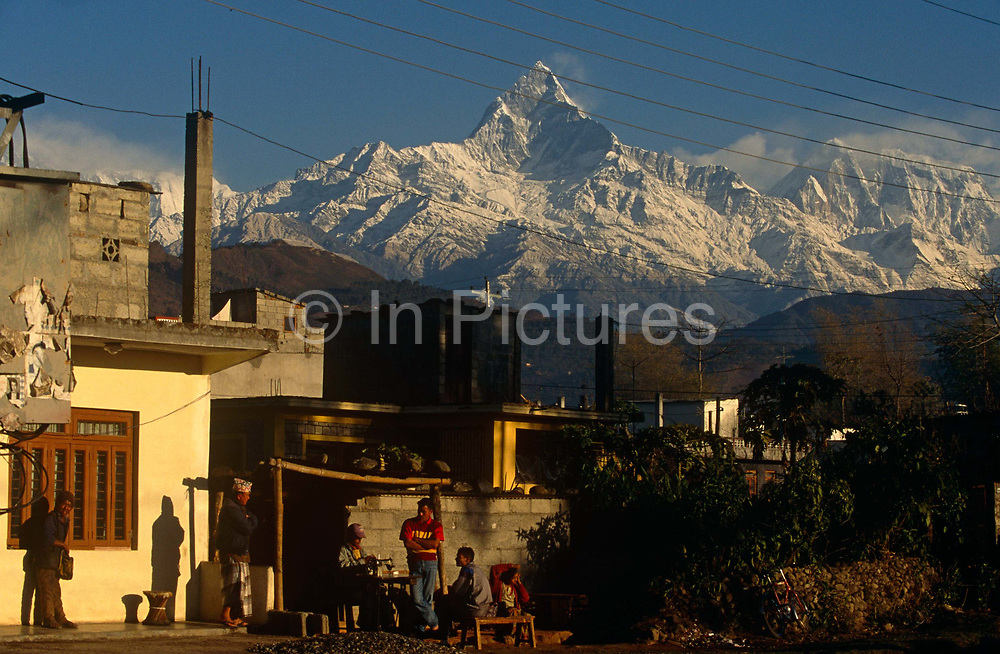 Beneath the snow-capped peak of Machapuchare (or Machhaphuchhare), otherwise known as the Fishtail, plus other peaks in this Himalayan Himal landscape, we see a group of Nepali locals chatting on low seats outside a home in the town of Pokhara, Nepal. The friends have a roughly-constructed dwelling that uses breeze bocks and concrete and we see a future attempt to make a first story extension. Machapuchare is revered by the local population as particularly sacred to the god Shiva and is therefore off limits to climbing. It's at the end of a long spur ridge, coming south out of the main backbone of the Annapurna Himal, that forms the eastern boundary of the Annapurna Sanctuary and the peak is about 25km north of Pokhara, the main town of the region.