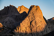 "Sunrise on Pingora Peak seen from Jackass Pass, Cirque of the Towers, Bridger Wilderness, Wind River Range, Bridger-Teton National Forest, Rocky Mountains, Wyoming, USA. We backpacked to Big Sandy Lake Campground (11 miles round trip with 1000 feet gain). Two hours before sunrise, I departed from Big Sandy Lake to reach Jackass Pass viewpoint for Cirque of the Towers and Lonesome Lake (6.5 miles round trip, 1860 ft gain) on the Continental Divide Trail. The Continental Divide follows the crest of the ""Winds"". Mostly composed of granite batholiths formed deep within the earth over 1 billion years ago, the Wind River Range is one of the oldest mountain ranges in North America. These granite monoliths were uplifted, exposed by erosion, then carved by glaciers 500,000 years ago to form cirques and U-shaped valleys."