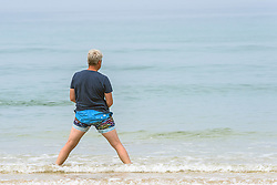 A man with a strange stance at Fistral Beach in Newquay, Cornwall.