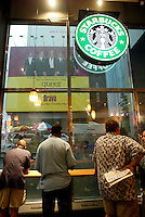 Aug 04, 2003; New York, NY, USA; Three men take shelter inside a Starbucks Coffee shop in Times Square during a summer thunderstorm. Scenic view of New York City.
