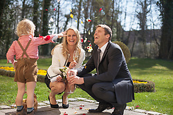 Son throwing flower petals on bride and groom, Munich, Bavaria, Germany