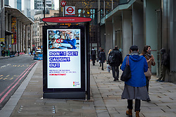 © Licensed to London News Pictures. 09/12/2020. LONDON, UK.  People walk by Brexit-related digital signage at a bus stop in the City of London.  London is currently in Tier 2 High Alert level, but it is reported that the city may move to Tier 3 Very High Alert level before Christmas as infections continue to rise across the capital.  Photo credit: Stephen Chung/LNP