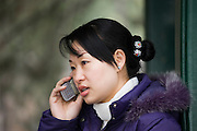 Woman chats on a mobile phone at The Summer Palace, Beijing, China