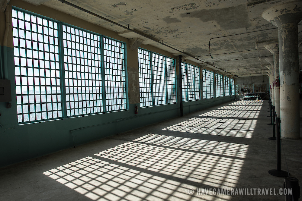 The sunlight casts sharp shadows from the bars on the windows of the Industries Building in the former prison complex of Alcatraz in San Francisco Bay.