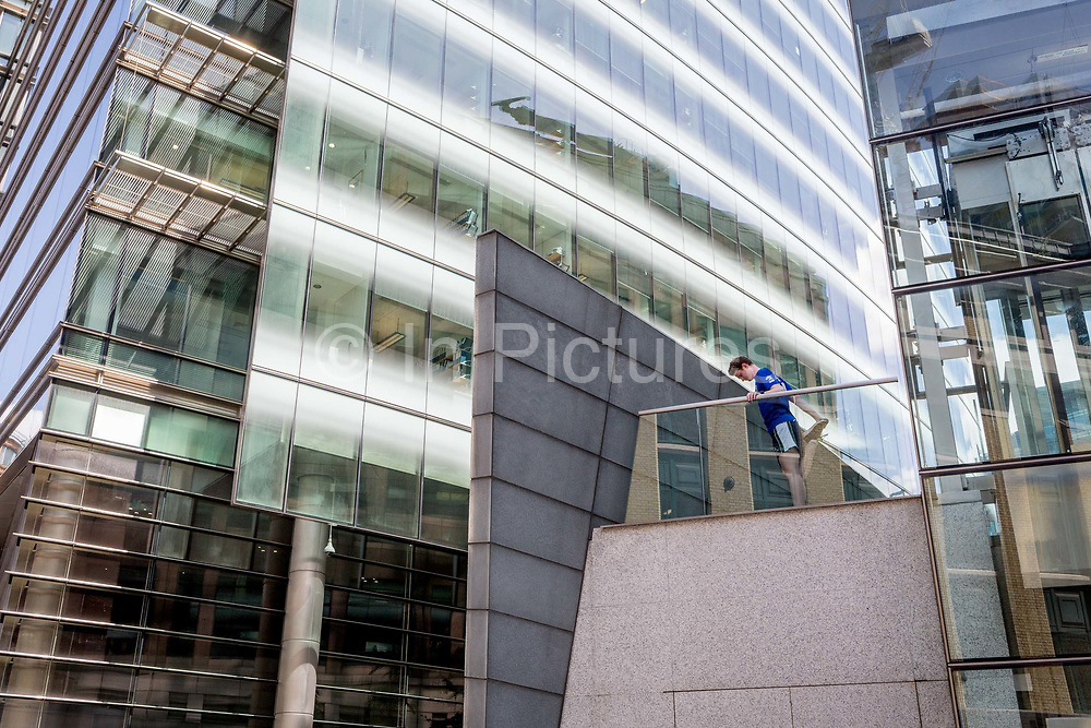 Beneath the architicture of modern corporate offices, a runner stretches his knee joints and muscles on the first level of a walkway at Broadgate in the City of London, the capitals financial district - aka the Square Mile, on 29th July 2019, in London, England.