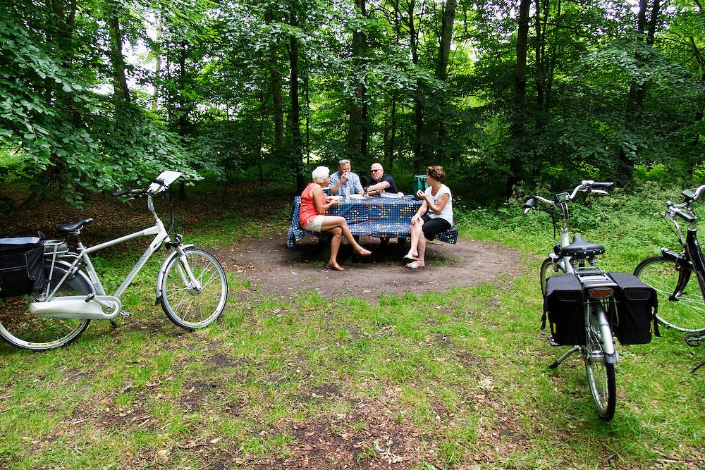 Bij Bosch en Duin pauzeren oudere fietsers bij een picknicktafel tijdens hun fietstocht.<br /> <br /> Near Bosch en Duin older cyclists pause at a picnic table on their cycle tour.