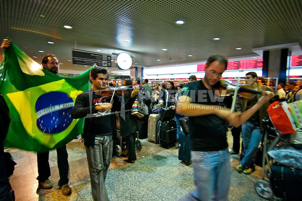 Músicos tocam o hino nacional no saguão do aeroporto internacional Slagado Filho que juntou mais de 2 mil pessoas após 10 horas de atrasos nos voos. FOTO: Jefferson Bernardes/Preview.com
