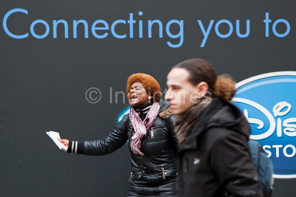 A female street preacher shouts religous fervour at passers by on a busy Oxford street, London.