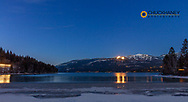 Lights from night skiing at Whitefish Mountain Resort and passing freight train reflect at Whitefish Lake State Park, Montana, USA