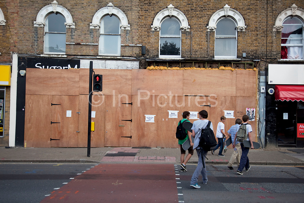 Closed up shop on Denmark Hill in South London. This is a very common site all over London and the rest of the country due to the recent economic downturn, struggling economy. This shop was selling off it's remaining stock at a makeshift shop on the street just around the corner.