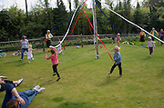 Children dance around a maypole at an English country festival, Shottisham, Suffolk, England