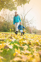 Mother and son kicking autumn leaves on grass