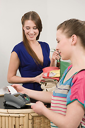 Sales girl with customer at cashpoint
