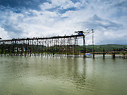 16 SEPTEMBER 2014 - SANGKHLA BURI, KANCHANABURI, THAILAND: Workers on the deck of the Mon Bridge. The 2800 foot long (850 meters) Saphan Mon (Mon Bridge) spans the Song Kalia River. It is reportedly second longest wooden bridge in the world. The bridge was severely damaged during heavy rainfall in July 2013 when its 230 foot middle section  (70 meters) collapsed during flooding. Officially known as Uttamanusorn Bridge, the bridge has been used by people in Sangkhla Buri (also known as Sangkhlaburi) for 20 years. The bridge was was conceived by Luang Pho Uttama, the late abbot of of Wat Wang Wiwekaram, and was built by hand by Mon refugees from Myanmar (then Burma). The wooden bridge is one of the leading tourist attractions in Kanchanaburi province. The loss of the bridge has hurt the economy of the Mon community opposite Sangkhla Buri. The repair has taken far longer than expected. Thai Prime Minister General Prayuth Chan-ocha ordered an engineer unit of the Royal Thai Army to help the local Mon population repair the bridge. Local people said they hope the bridge is repaired by the end November, which is when the tourist season starts.    PHOTO BY JACK KURTZ