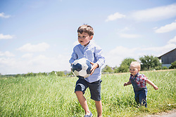 Small boy playing football with his brother on meadow in the countryside, Bavaria, Germany