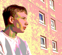Portrait of teenager wearing sweatshirt sitting alone in front of flats,