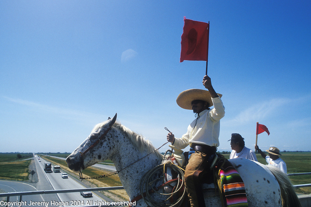 (Copyright 2004 Jeremy Hogan) All rights reserved.Latinos cross Highway 99 on horses several miles south of Sacramento, where a month long, 350-mile march would culminate in a rally on the steps of California's state capitol.