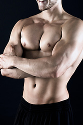 Close-up of shirtless muscular man with arms crossed