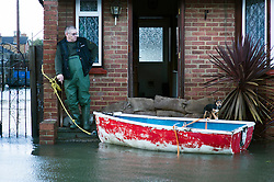 © London News Pictures. 12/02/2014. Egham, UK.  A man and his dog stand next to a boat outside a property surrounded by flood water  in Egham in Surrey. Torrential rain in the area is due to raise water levels increasing the risk of further flooding. Photo credit : Ben Cawthra/LNP
