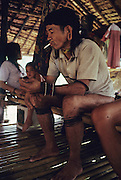 PENAN, MALAYSIA. Sarawak, Borneo, South East Asia. Penan smoking cigarette. Tropical rainforest and one of the world's richest, oldest eco-systems, flora and fauna, under threat from development, logging and deforestation. Home to indigenous Dayak native tribal peoples, farming by slash and burn cultivation, fishing and hunting wild boar. Home to the Penan, traditional nomadic hunter-gatherers, of whom only one thousand survive, eating roots, and hunting wild animals with blowpipes. Animists, Christians, they still practice traditional medicine from herbs and plants. Native people have mounted protests and blockades against logging concessions, many have been arrested and imprisoned.
