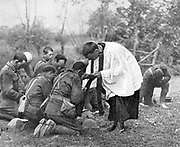 World War I: New Zealand troops taking Holy Communion administered by an Army chaplain in the open air.