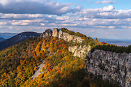 The cascade of colorful autumn foliage adorns the mountain top and cliff lines leading to Chimney Rock of North Fork Mountain in West Virginia on a sunny day.