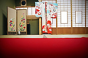 NARA, JAPAN,  - Red an blue cermonial Kimono For the 18 years old ceremony. The kimono is hang in front of soji window with a red carpet in the middle of the room ;  JULY 2005. ***[FR]*** Un kimono de ceremonie bleu et rouge au motif floraux suspendu a une fenetre en soji, en premier plan un tapis rouge