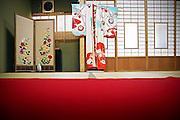 NARA, JAPAN,  - Red an blue cermonial Kimono For the 18 years old ceremony. The kimono is hang in front of soji window with a red carpet in the middle of the room ;  JULY 2005. ***[FR]*** Un kimono de ceremonie bleu et rouge au motif floraux suspendu a une fenetre en soji, en premier plan un tapis rouge