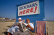 An elderly couple sit in peace on a quiet beach in the seaside resort of Great Yarmouth, Norfolk. In a classic English beach holiday scene, the husband and wife relax, reclining in a pair of deckchairs at a kiosk that dispenses these quaintly British beach chairs. A sign telling other holidaymakers to collect and pay for their time in them appears on the freshly-painted clap-board wall. As the lazy completes word puzzles in her magazine, the gentleman reads his regular copy of the Daily Mirror tabloid newspaper. He is tanned, perhaps spent his summer tending his garden back home but here on holiday, they both have the chance to spend some time together away from home, in a resort known for its beaches and coastal adventures.