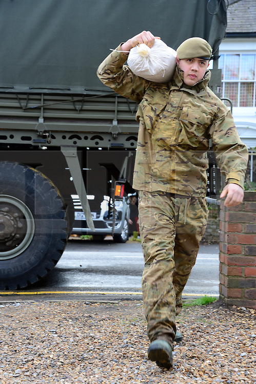© Licensed to London News Pictures. 13/02/2014. Chertsey, UK. Soldiers from the Royal Welsh have been helping members of the public in Chertsey. With the river Thames still rising, they have been providing and placing sandbags on the Chertsey Bridge Road. . Photo credit : Russ Nolan/LNP