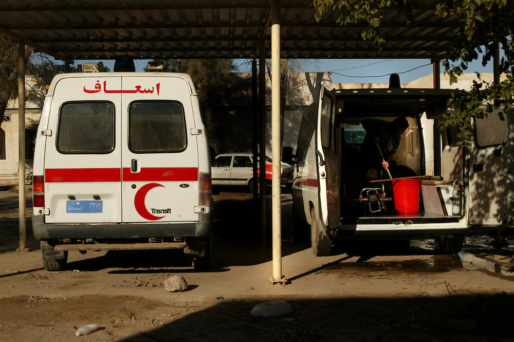 Hospital workers clean the inside of the ambulances used to transport wounded people from the scene of an explosion, Iskandariyah, Iraq, Feb. 10, 2004. A truck packed with an estimated 500 pounds of explosives blew up at a police station. Dozens of would-be recruits were lined up to apply for jobs at the station. A hospital official said at least 50 people were killed and 50 others wounded. The local Iraqi police commander, Lt. Col. Abdul Rahim Saleh, said the attack was a suicide operation, carried out by a driver who detonated a red pickup as it passed the station.