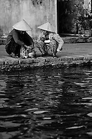 two women wearing conical hats chat on Hoi An's historic waterfront.