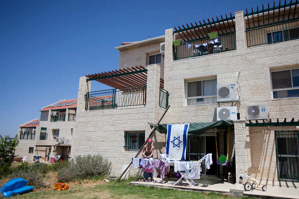 An Israeli Jewish settler hangs her clean laundry outside her home, which is scheduled for evacuation and demolition, at the Ulpana neighborhood in the Jewish settlement of Beit El near the Palestinian West Bank city of Ramallah, on April 27, 2012. Israel's State Attorney Office petitioned to the High Court of Justice requesting to postpone the scheduled evacuation, and demolition, of five structures that were built on land classified as private Palestinian property in the Ulpana neighborhood in the Beit El settlement, originally due to take place on May 1, by three months.
